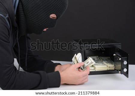 Thief burglar stealing money during home safe codebreaking - stock photo