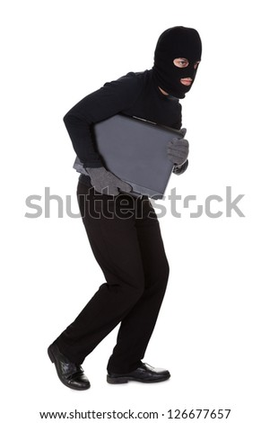 Thief dressed in black and wearing a balaclava stealing a laptop computer and making a furtive escape isolated on white