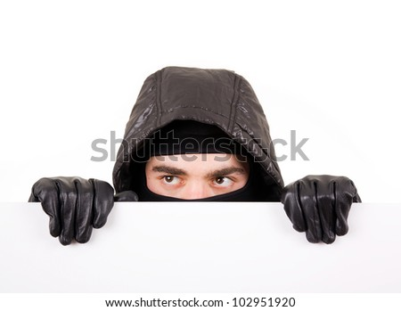 Thief hiding under a white wall - stock photo