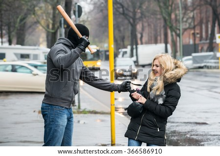 Thief hitting woman with baseball bat while trying to steal purse on sidewalk during winter - stock photo