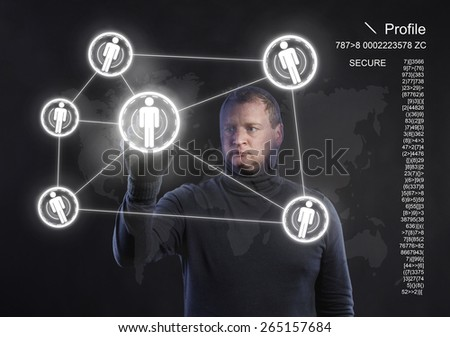 Thief in action stealing information with balaclava on his face, dressed in black. Studio shot on black background.