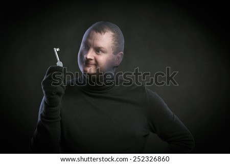 Thief in action with balaclava on his face, dressed in black. Studio shot on black background. - stock photo