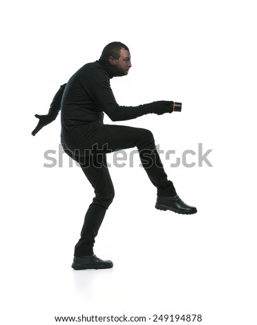 Thief in action with balaclava on his face, dressed in black. Studio shot on white background. - stock photo