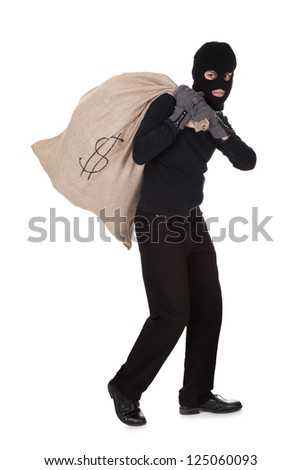 Thief in black clothes wearing a balaclava carrying a large bag of money with a dollar sign over his shoulder isolated on white