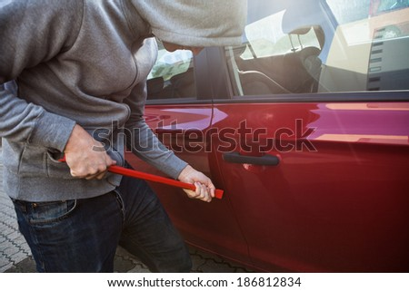 Thief in hooded jacket opening car's door with crowbar - stock photo