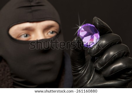 Thief. Man in black mask with a big diamond.Focus on diamond - stock photo