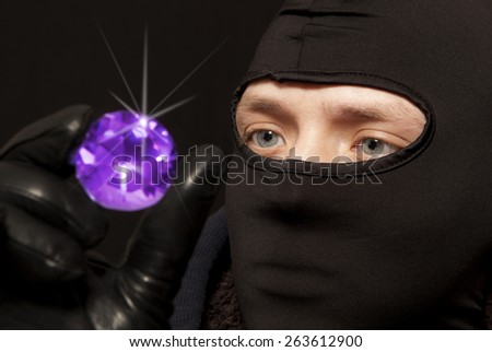 Thief. Man in black mask with a big emerald. Focus on thief - stock photo
