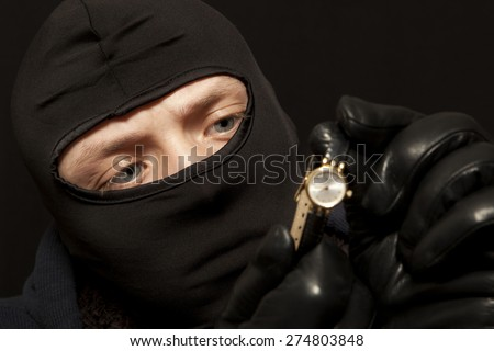 Thief. Man in black mask with a golden watch. Focus on thief - stock photo
