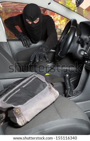 Thief stealing a handbag from a woman in a car - stock photo