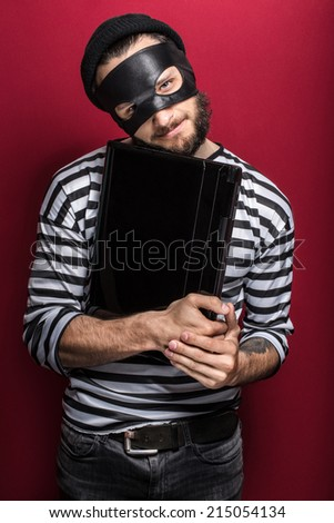 Thief stealing a laptop computer. Portrait on red background   - stock photo