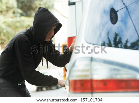 Thief stealing automobile car at daylight street in city - stock photo