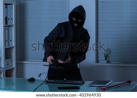 Thief Stealing Computer From Office At Night - stock photo