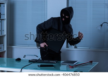 Thief Stealing Computer With Laptop And Digital Tablet On Office Desk - stock photo