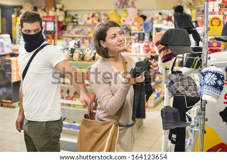 Thief stealing from handbag of a woman in a store - stock photo
