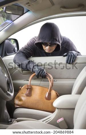 thief stealing handbag from car - stock photo