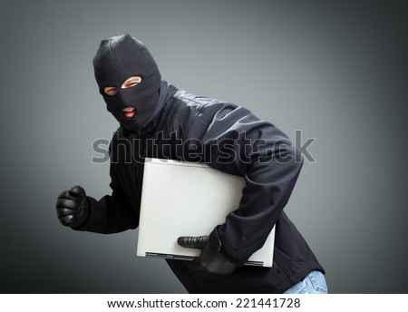 Thief stealing laptop computer concept for hacker, hacking, security or insurance - stock photo