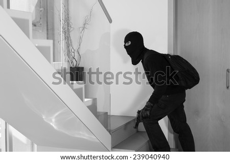Thief stealing private house with a gun in hand - stock photo