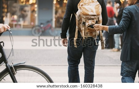 Thief stealing wallet from backpack of a man walking on street during daytime.  Pickpocketing on the street during daytime - stock photo