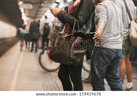 Thief stealing wallet from purse of a woman using mobile phone at the subway station. Pickpocketing at subway station - stock photo