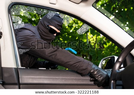 Thief successfully breaking a vehicle's window. - stock photo