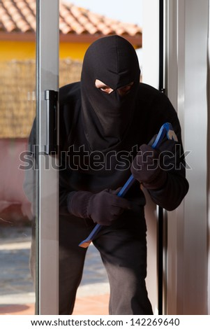 Thief trying to force a window to rob a house - stock photo