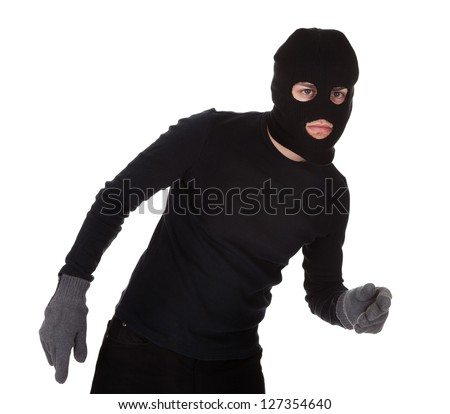 Thief wearing a balaclava dressed in blacked moving stealthily. Isolated on white