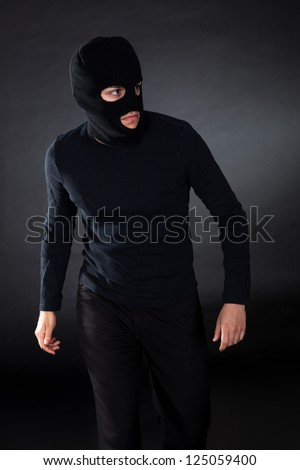 Thief wearing a balaclava dressed in blacked moving stealthily through the darkness as he prepares to commit robbery - stock photo