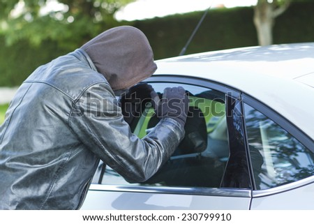 Thief wearing black clothes and leather coat stealing a car - stock photo
