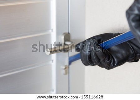 Thief with a bar of iron in the hand to open a door - stock photo