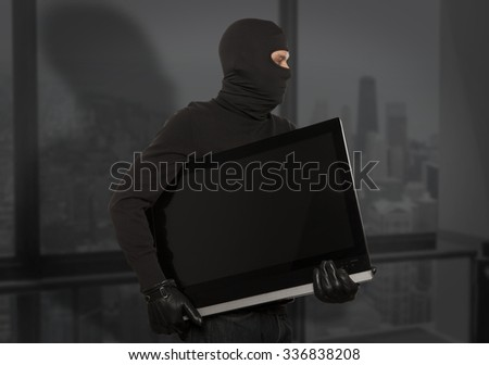 Thief with balaclava stealing computer monitor or television  - stock photo