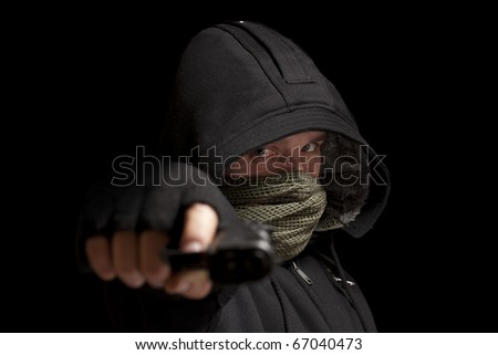 Thief with gun aiming into a camera - stock photo