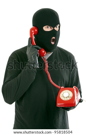 Thief with mask red with a phone call - stock photo
