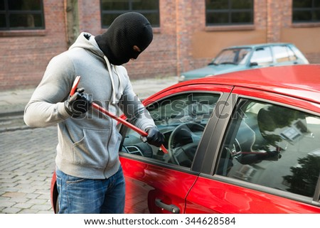 Thief With Mask Trying To Smash The Window Of The Car With Crowbar - stock photo