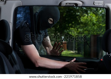 Thief with obscured face open car lock - stock photo