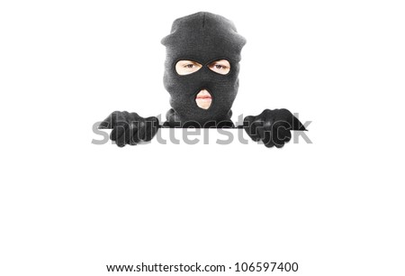 Thief with robbery mask holding blank white board with room for your safety message isolated on white background