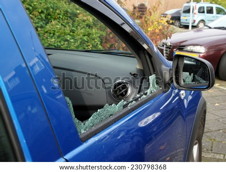 Thiefs have broken a car window to steel items inside - stock photo
