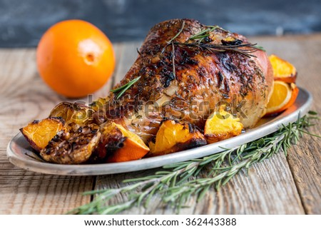 Thigh of turkey baked with oranges on a metal plate.