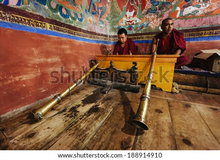 THIKSEY, INDIA - SEPTEMBER 4, 2011: Tibetan Buddhist monks with Tibetan horn (dungche) during prayer in Thiksey gompa (Buddhist monastery)  of Gelugpa sect - the largest gompa in central Ladakh - stock photo