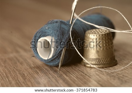 thimble and needles for sewing close-up on a background thread spools. macro