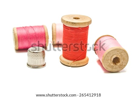 thimble and spools of thread on white background - stock photo