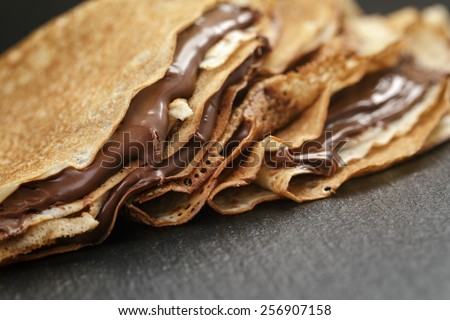 thin crepes or blinis with chocolate cream on slate board - stock photo