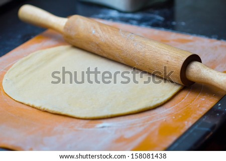 Thin dough for pasta or pizza on table with rolling pin - stock photo