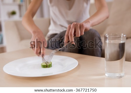 Thin girl is sitting on the sofa with an empty plate which is closeup on the photo. Malnutrition harms health - stock photo
