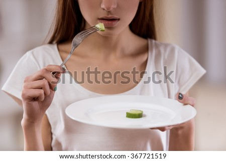 Thin girl with an empty plate standing in the center of the room closeup, malnutrition harms health.