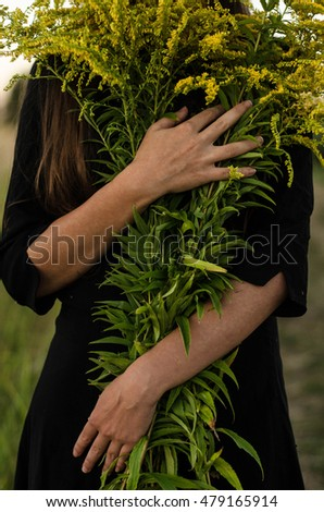 thin hands of a young girl who embrace a large bouquet of yellow flowers