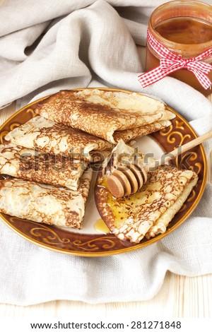 Thin pancakes, crepes with  syrup on wooden cutting board. Pancake week, mardi gras, maslenitsa holidays - stock photo