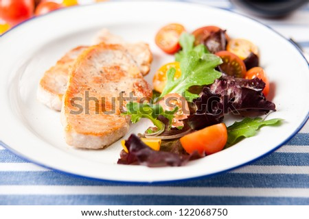 Thin Pork Chops Served with Sauteed Potatoes, Green Beans, Cherry Tomatoes and Greens - stock photo