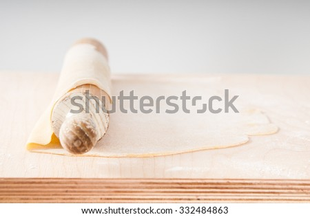 Thin sheet of fresh pasta dough with rolling pin