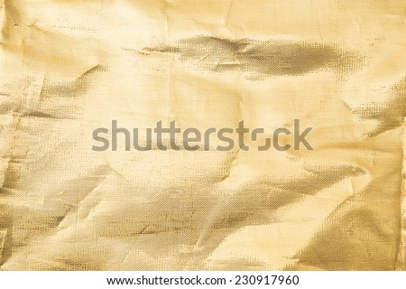 Thin shiny golden cloth background with shiny uneven surface with drapery and wrinkles - stock photo
