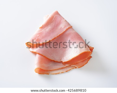 thin slice of ham folded on white background